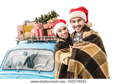 happy young couple covered in plaid standing in front of blue car with christmas gifts isolated