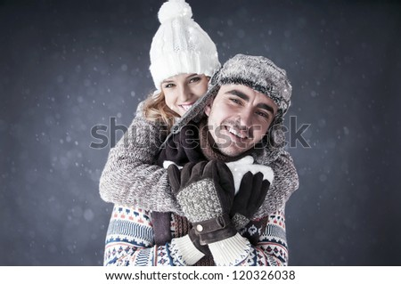 Happy young couple   covering  snow background