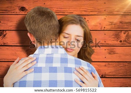 Happy young couple cuddling each other against pink paint splashed surface #569815522