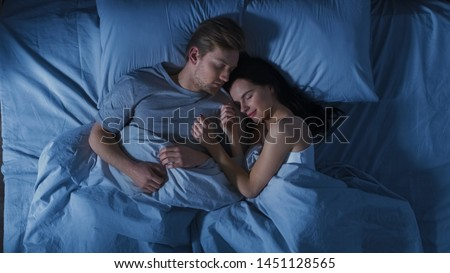 Happy Young Couple Cuddling Together in the Bed Sleeping at Night. Beautiful Girl and Handsome Boy Sleeping Together, Sweetly Embracing Each other. Top Down Shot.