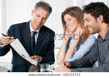 Happy young couple discussing with a financial agent their new investment