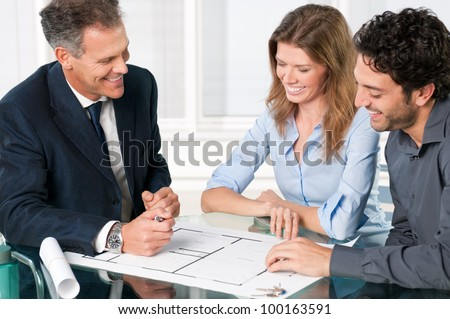 Happy young couple discussing with an estate agent about their new house plans