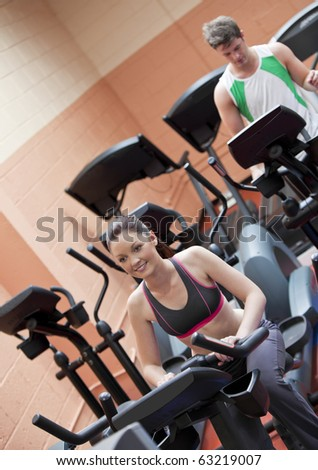 Happy young couple doing exercises using equipments in a sport centre