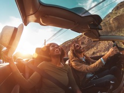 Happy young couple doing road trip in tropical city - Travel people having fun driving in trendy convertible car discovering new places - Relationship and youth vacation lifestyle concept