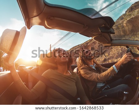 Happy young couple doing road trip in tropical city - Travel people having fun driving in trendy convertible car discovering new places - Relationship and youth vacation lifestyle concept Foto stock ©