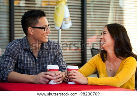Happy young couple drinking coffee outside cafe
