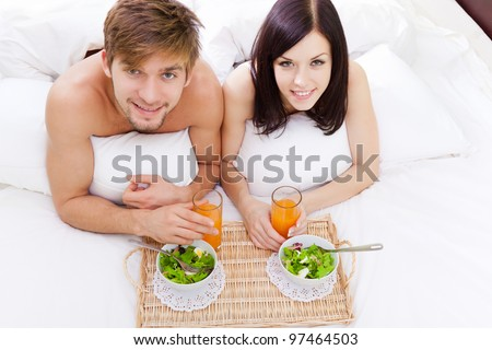 happy young couple eat breakfast in bed in morning, lovely couple lying in a bed, happy smile looking at camera, concept of honeymoon, valentine day top angle view
