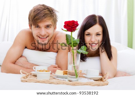happy young couple eat breakfast in bed in morning with red rose flower, lovely couple lying in a bed, happy smile looking at camera, concept of honeymoon, valentine day