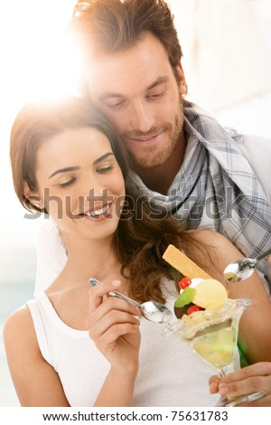 Happy young couple eating icecream on summer beach, smiling.?