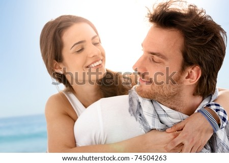 Happy young couple embracing on summer beach, having fun together, laughing.?