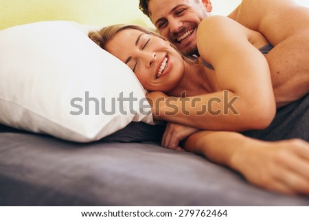 Happy young couple embracing while lying next to each other on bed. Caucasian couple smiling in bed together. Couple waking up.