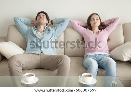 Shutterstock Happy young couple enjoying sitting on sofa at home, resting hands behind the head, relaxing with eyes closed, cup of coffee in the morning, dreaming of vacation, listening to music, leisure lazy day