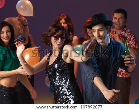 happy, young couple flirting and dancing on the dancefloor in a night club