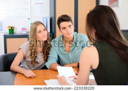 happy young couple getting advice in office with beautiful business woman