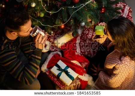 Happy young couple giving present and drinking tea at home at Chrismas time. Christmas tree and gift boxes. Top-down composition