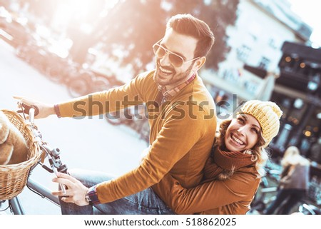Happy young couple going for a bike ride on a autumn day in the city.
