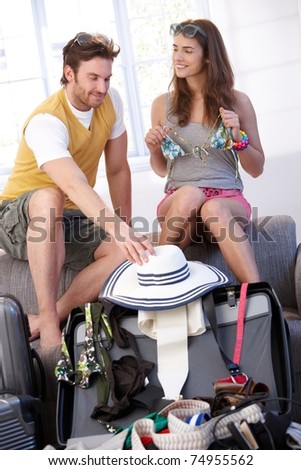 Happy young couple going to summer vacation packing suitcase at home.?