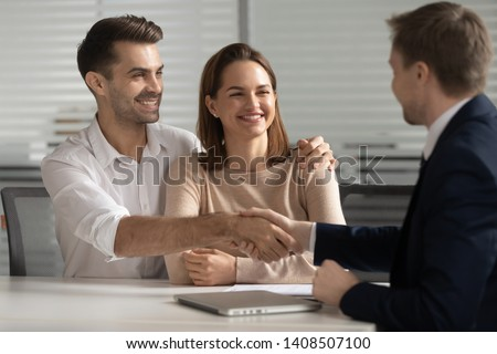 Happy young couple handshake lawyer insurer broker make financial business deal, smiling satisfied family shake hand of realtor insurer thanking for consulting buying insurance services at meeting
