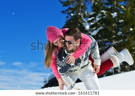 Happy young couple has fun on fresh snow at beautiful winter sunny day on vacation