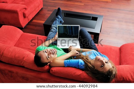 happy young couple have fun and relax at comfort bright apartment and work on laptop computer happy young couple have fun and relax at comfort bright apartment and work on laptop computer - stock photo