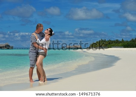 happy young couple have fun and relax at summer vacation on background maldives travel location and beautiful white sand beach
