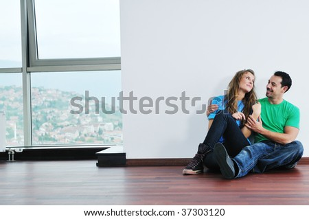 happy young couple have fun and relax in their new big bright home apartment