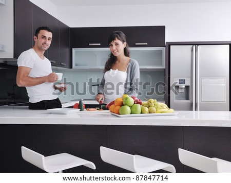 happy young couple have fun in  modern kitchen indoor  while preparing fresh fruits and vegetables food salad