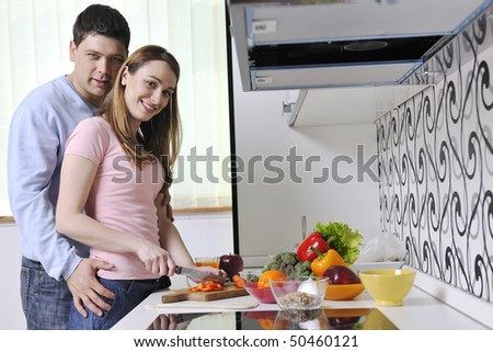 happy young couple have fun while preparing healthy fresh food in kitchen