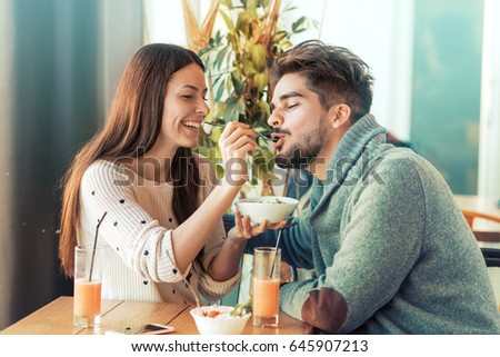 Happy young couple having breakfast in cafe,enjoying together. #645907213