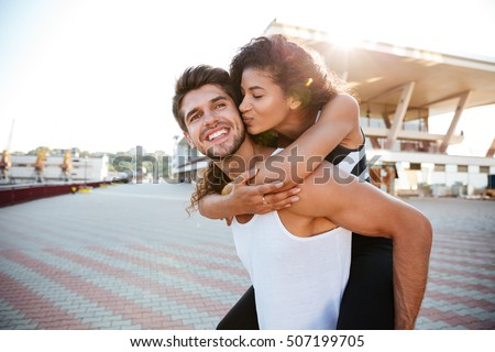 Happy young couple having fun and kissing outdoors