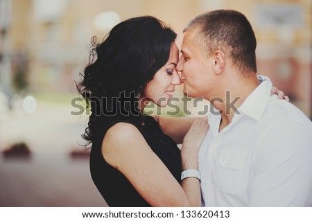 Happy young couple having fun, guy kissing his girlfriend