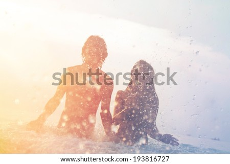 happy young couple having fun, man and woman in the sea on the beach. vintage retro style with soft focus and sun flare #193816727