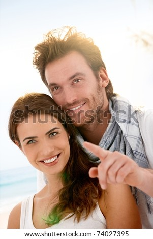 Happy young couple having fun on summer beach, looking away, smiling.?