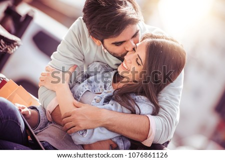Happy young couple having fun outdoors and smiling. - Shutterstock ID 1076861126