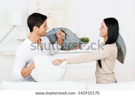 Happy young couple having pillow fight in house