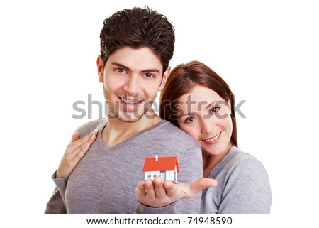 Happy young couple holding a miniature house in their hand