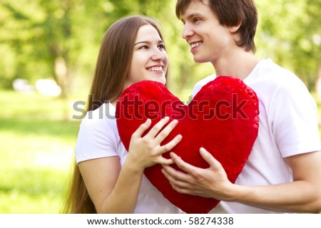 happy young couple holding big red heart outdoor