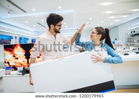 Happy young couple holding big TV box in electronic store. Smiling and celebrating successful shopping.