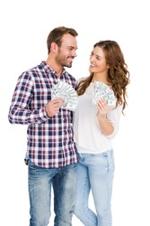 Happy young couple holding fanned out currency notes on white background