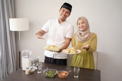 happy young couple holding opor ayam and ketupat for lebaran or eid mubarak
