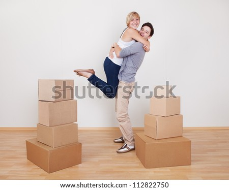 Happy young couple in a close ecstatic embrace smiling happily as they stand surrounded by cartons in their new home