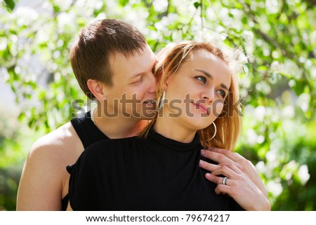 Happy young couple in a spring garden - stock photo