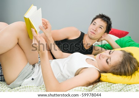 Happy young couple in bed reading a book