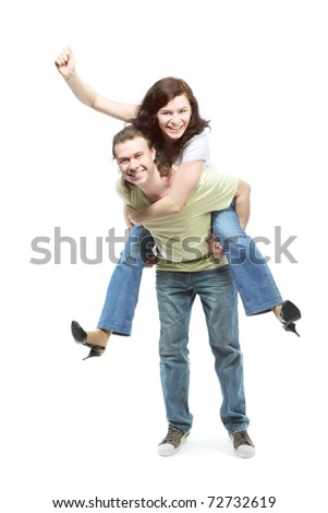 Happy young couple in jeans, funny girl jumps on boyfriend back