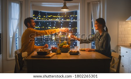 Photo of  Happy Young Couple in Love Have Romantic Dinner, Toasting Each other with Glasses of Wine, Eating Tasty Meal in the Kitchen, Celebrating, Talking. Beautiful Lovely Husband and Wife Have Romantic Time