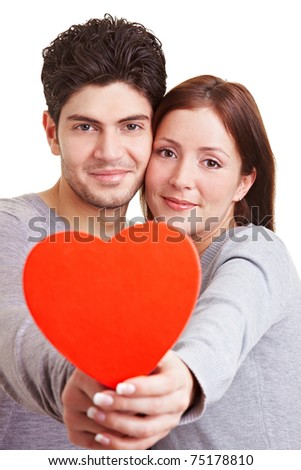 Happy young couple in love holding a red heart