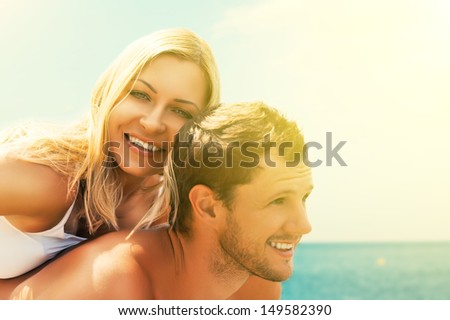happy young couple in love hugging and laughing on the beach at Sea