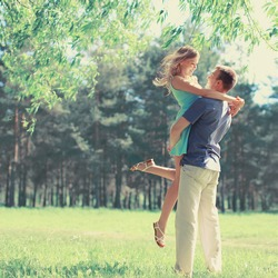 Happy young couple in love hugging enjoys spring day, loving man holding his woman carefree outdoors at park, joyful moment