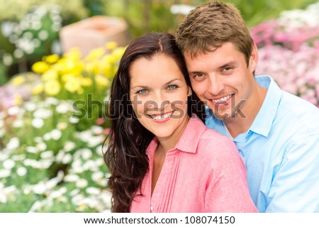 Happy young couple in love hugging in nature garden