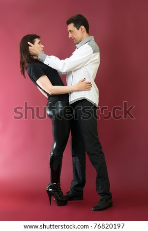 Happy young couple in love on red burgundy background